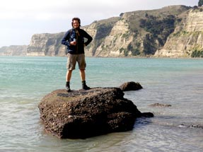 Thomas stands on a rock in the sea